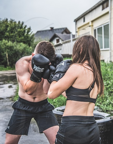Young man training kickbox with young girl outside old building in the rain. photo