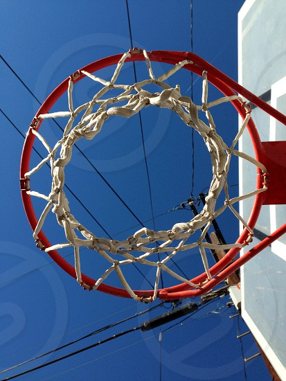 low angle photography of white and red basketball hoop under blue sky and black cable wires during daytime photo