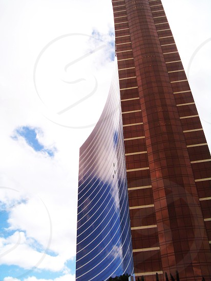 view of tall building and white clouds photo