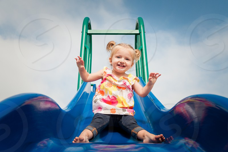 Happy little girl coming down the slide at the park photo