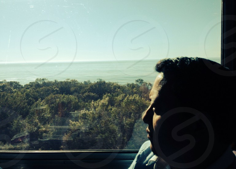 person by window looking at ocean photo