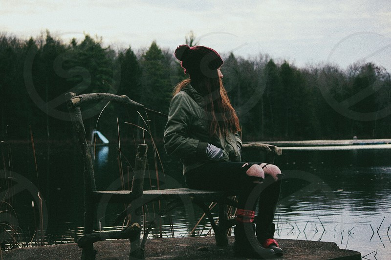 woman in gray jacket wearing black distressed denim pants sitting on bench on dock near swamp photo