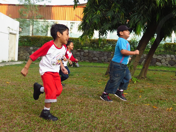 Kindergarten Boys Run and Play Happily in The Park. Daytime Horizontal Happy Indonesia Color Green Grass Joyful Lifely photo