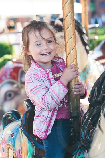 Little adorable smiling girl riding a horse on roundabout carousel at funfair photo