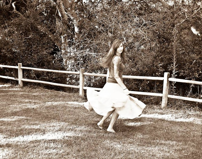 Young woman twirling and dancing in a park Santa Barbara California USA photo