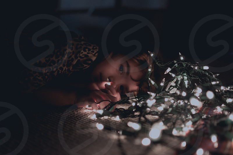 girl in brown and beige leopard shirt face lying on floor beside a turned on christmas light photo