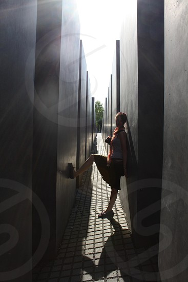 woman wearing gray tank top poses in the middle of monoliths during daytime photo