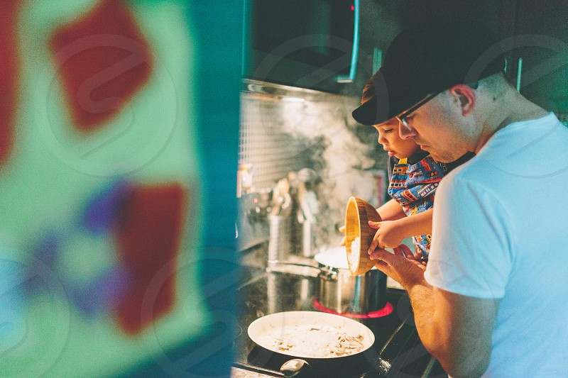 A father and son preparing dinner in their kitchen.  photo