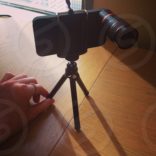 black smartphone with camera lens on small tripod photo