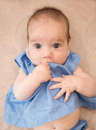 baby surprised expressive hand in mouth infant photo