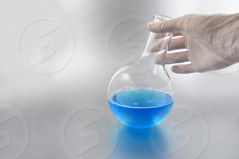 Round bottom boiling flask. Round bottom boiling flask with blue liquid. Hand holding laboratory glass photo