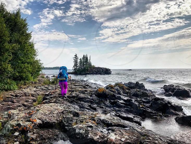 Backpacker along rocky shoreline photo