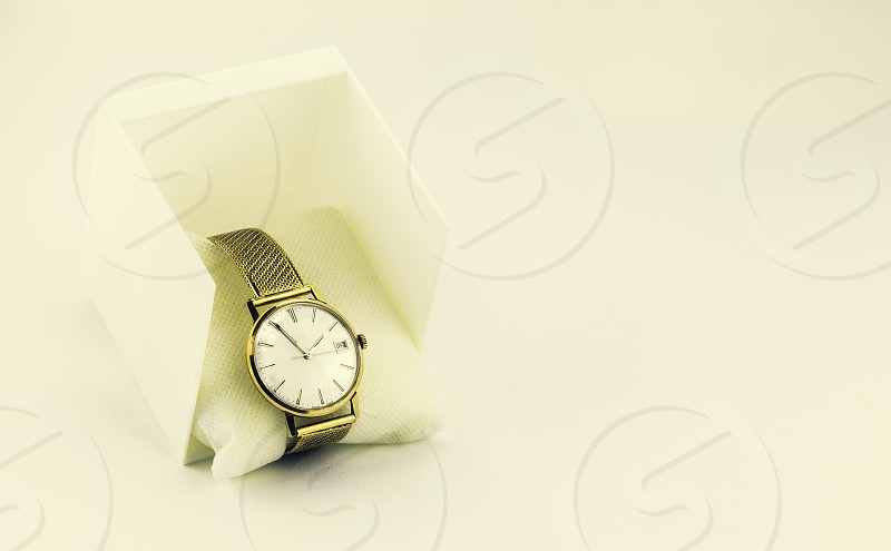 Gold Automatic vintage wristwatch on white background  showing 13:55 on the 25st photo