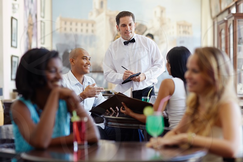 waiter; restaurant; people; couple; dating; dining; man; 30s; 20s; adult; african; amusement; beautiful; black; boyfriend; brunette; choosing; elegant; enjoy; female; friends; girlfriend; girls; guy; happiness; happy; hispanic; husband; indoor; joy; latin; latino; love; male; menu; occupation; ordering; persons; romantic; sitting; smiling; talking; together; wife; woman; women; worker; working; writing; young photo