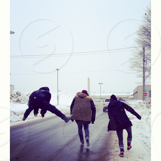Three teenagers two boys and one girl run and jump on the street in the winter in Gatineau Quebec Canada photo