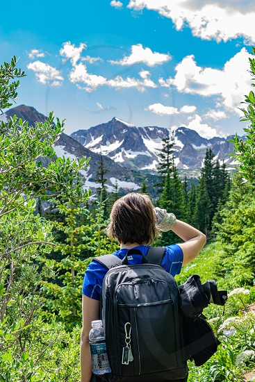 woman hiker with backpack looking over the trees to a mountain range. hiking colorado mountains in the summer photo