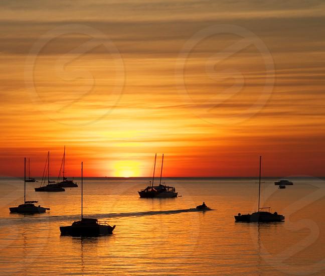 Darwin Sunset. sunset over water boats yachts boat yacht sunset orange calm peaceful sky clouds  photo