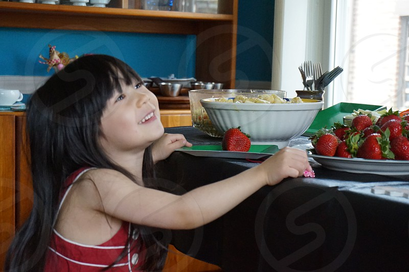 girl smiling holding table with strawberries in front photo