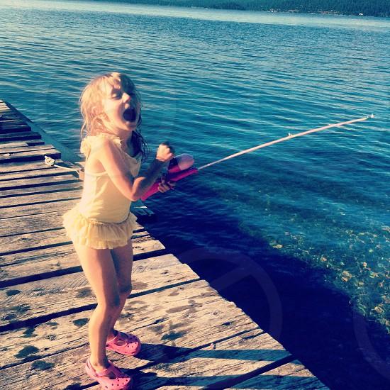 girl standing on wooden foot bridge beside sea photo
