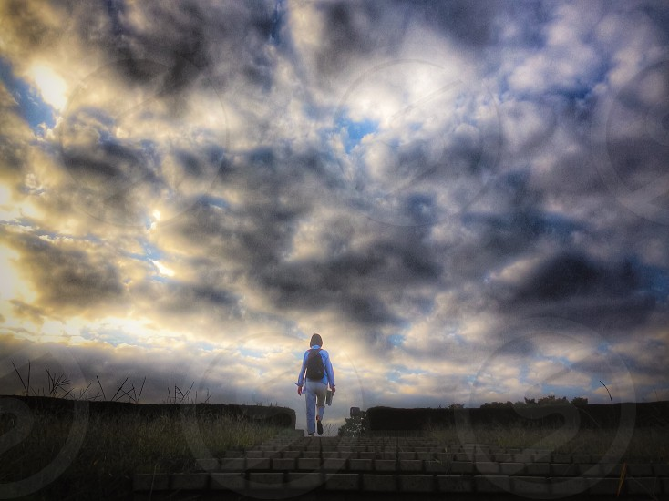 woman going up stairs cloud cover photo