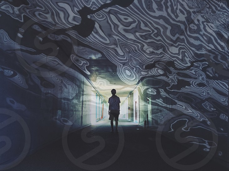 person standing on hallway with wall graffiti art photo