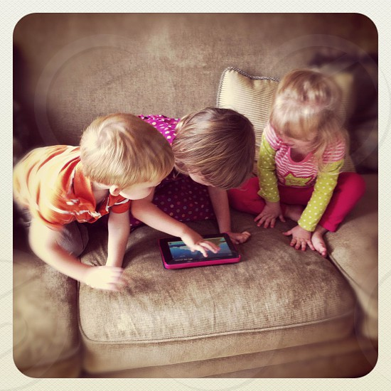 toddlers playing on the ipad photo