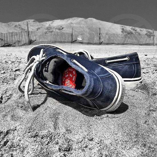 dark blue sperry topsider boat shoes sitting on beach sand photo