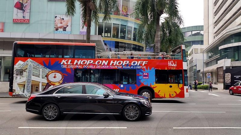 black sedan near red bus photo
