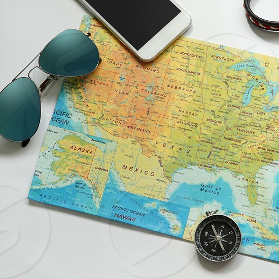 Travel items for a holiday map mobile sunglasses wallet compass and a few more. photo