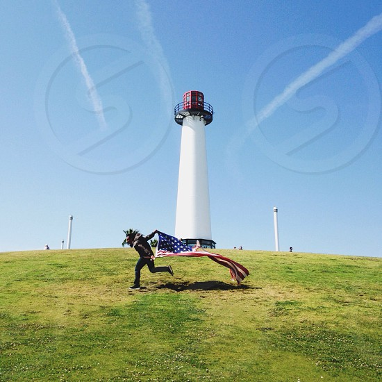 man racing flag near light house photography photo