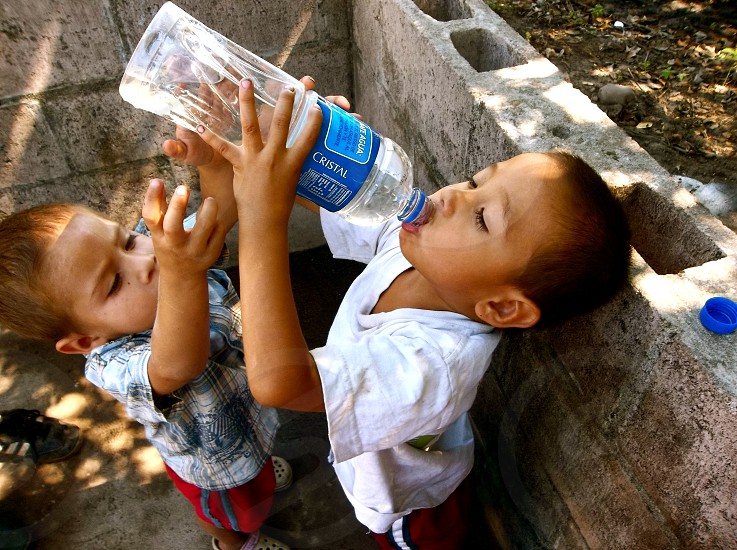 Dame Agua Water El Salvador Mission Trip Church Love Compassion Boys Drinking Water Bottle Share Young photo