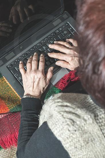 Old women using old laptop photo