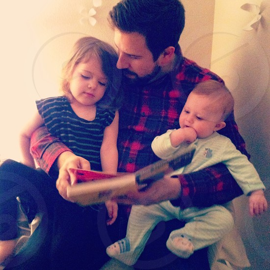 man in black and red plaid button down shirt holding two young children while reading to them photo