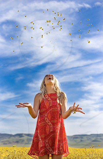 Spring girl blonde model flowers throw blue sky field photo