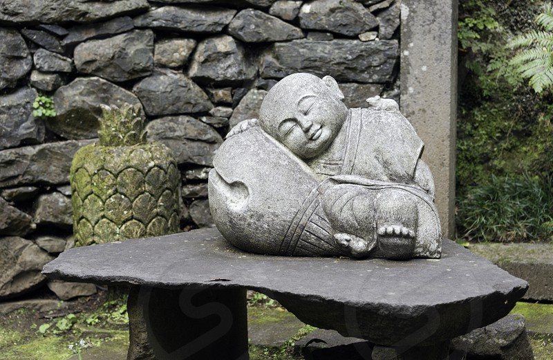 sleeping young buddha statue in garden with green plants and wall with rocks photo