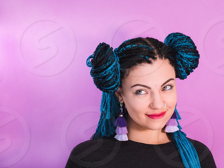 Glamour portrait of sexy woman with african blue braids hairstyle bindi nose ring and tassel earrings isolated on colorful background. photo