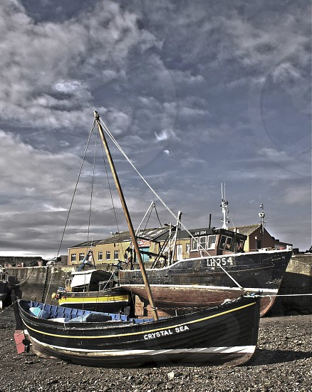 Vintage fishing boats up on sand in Scottish harbor photo