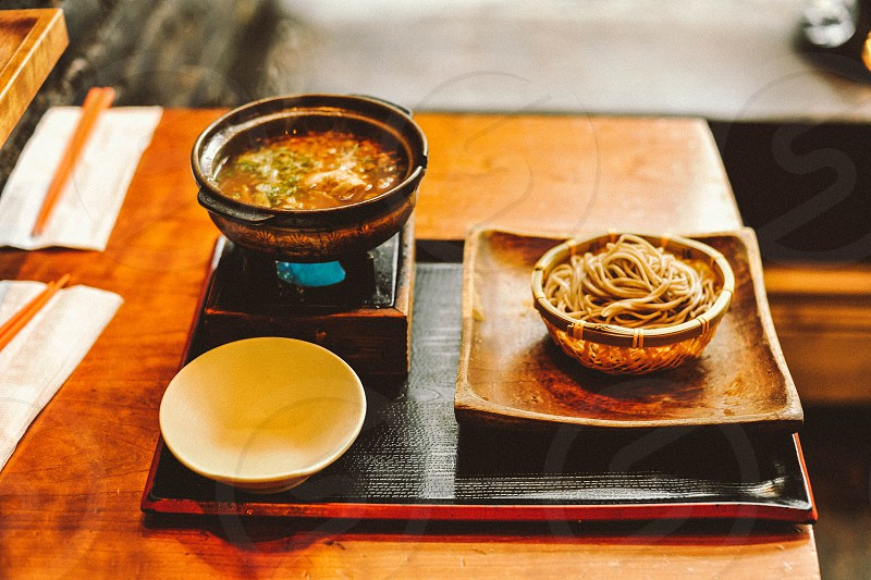 noodles in a bowl on a square wood plate on a serving platter with a bowl of soup photo