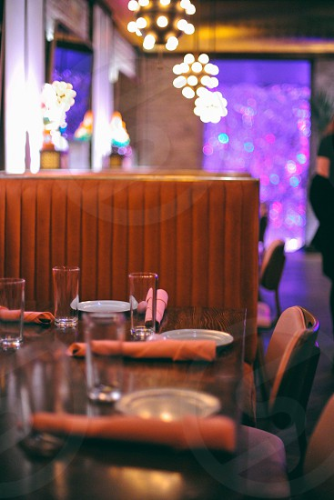 interior restaurant view with booths and set tables under hanging decorative photo