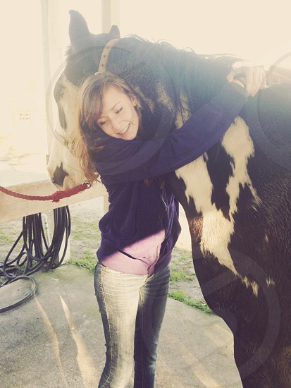woman hugging black and white horse photo