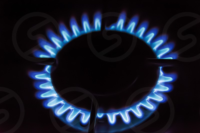 Gas burning on the stove. Blue flame of gas on a dark background photo