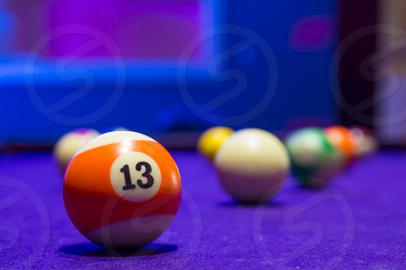 Billiard balls in a pool table. focus on the orange number 13 ball. photo