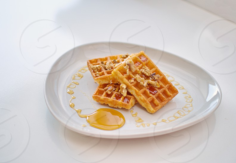 Whole grain waffles with Pecans and maple syrup for a healthy breakfast photo