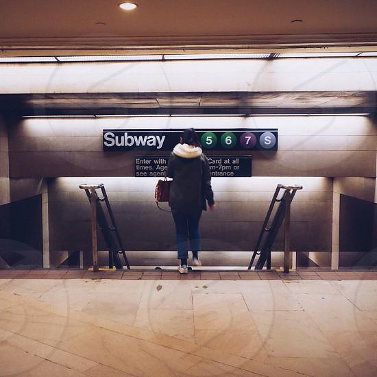 woman with handbag and black hooded coat entering subway 5 6 7 s photo