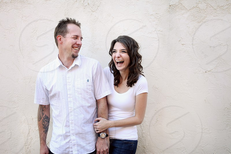 A young couple holds hands and laughs in front of a stucco wall. photo
