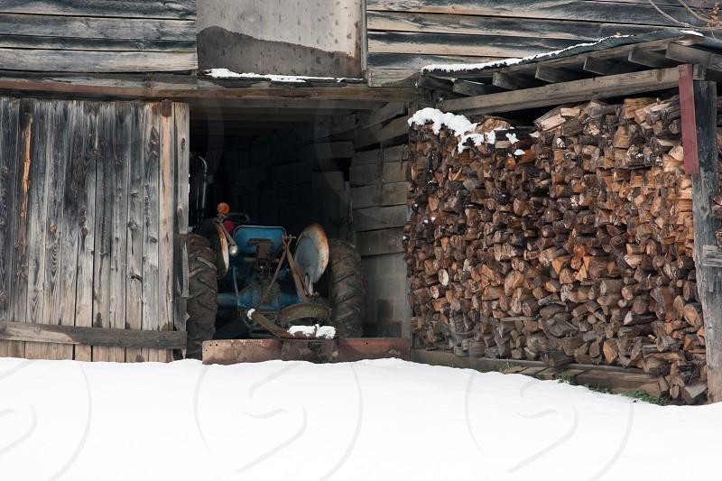 barn tractor wood split stack snow photo