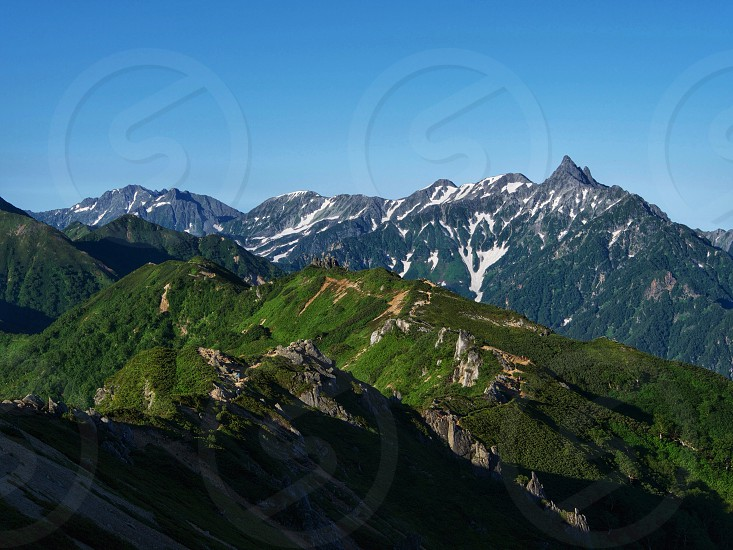 green mountains with blue sky background landscape photograph photo