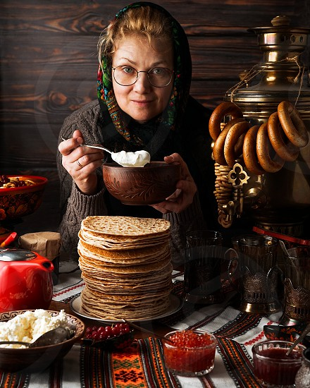 Woman at a table served according to Russian traditions with stacked pancakes and tea photo