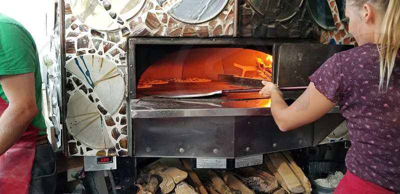 Chefs at work placing pizza in wood fired oven. photo