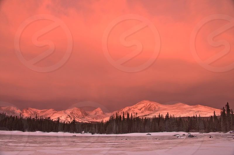 storm snow lake frozen pink orange mountains colorado pines blustery indian peaks wilderness area clearing sunrise usa photo